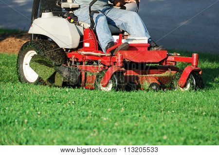 worker operating mower to mow the lawn
