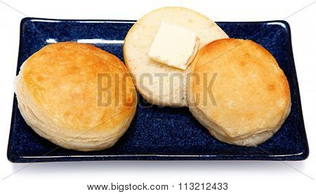 Golden Brown Fluffy Buttermilk Breakfast Biscuits with Butter on Blue Dish with White background.