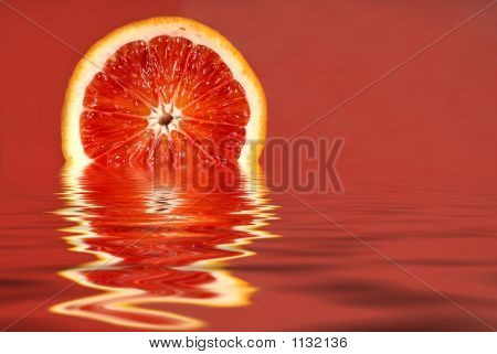 Half Of A Blood Orange In Water On A Red Background
