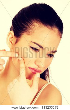 Unhappy teenage woman squeezing pimple on cheek.