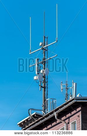 GSM radio satellite antenna on a mountain house cottage in the alps poster