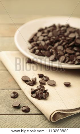 Chocolate morsels on plate, on wooden board