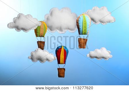 Fleece clouds and balloons on light blue background