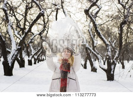 Soft and blur conception.Young beautiful girl close up in winter park enjoys snow fell