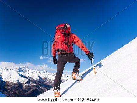 Climber walks up a snowy slope. Winter season, clear sky. In background the Monte Rosa massif, Italy, Europe.