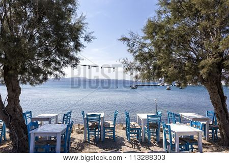 Traditional Greek Taverna On The Seafront On The Beach - Bright Chairs And Table At Milos Island, Gr