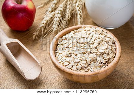 Rolled oats in bowl, red apple and milk