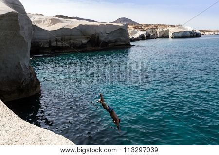 Tourists Jump In The Clear Water Of Sarakiniko Beach In Milos, Greece. This Beach Is One Of The Most