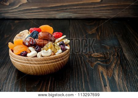 Mix of dried fruits and nuts on dark wood background with copy space. Symbols of judaic holiday Tu B