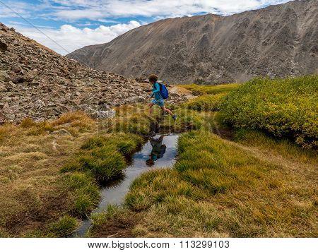 Woman jumps across creek