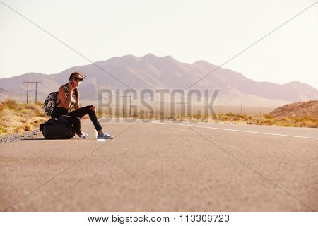 Woman On Vacation Hitchhiking Along Road Using Mobile Phone