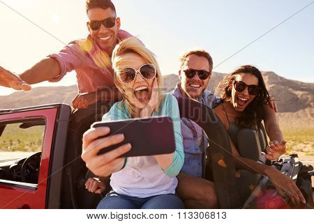 Friends On Road Trip In Convertible Car Taking Selfie poster