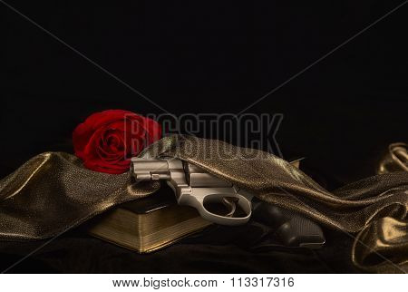 Snubnose revolver laying across gold bound book draped with Satin and a Red Rose poster