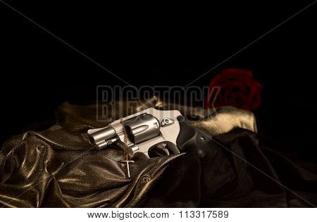 Snubnose 38 revolver laying across gold satin with a gold cross and black velvet an a red rose in the background with shallow depth of field poster