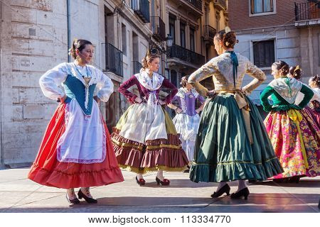 VALENCIA, SPAIN - FEBRUARY 08, 2015: unidentified women in traditional costumes perform a traditional dance on the Plaza de la Virgen in Valencia. Valencia is the 3rd largest city in Spain.