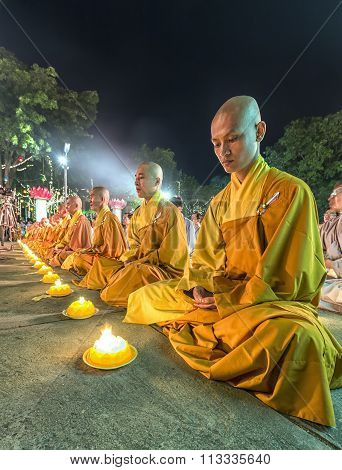 Buddhist monks meditate inside the candle in the night