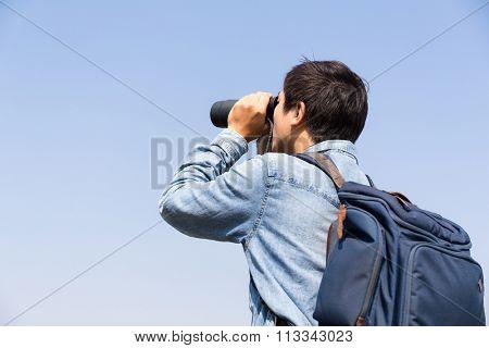 Man looking though the binocular against blue sky