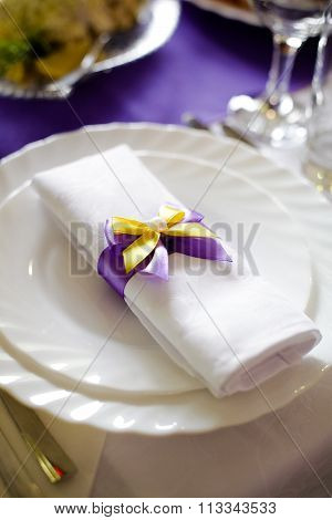 Wedding doily white with purple, yellow bowknot, decoration on the plate on the table