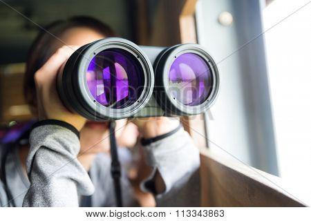 Asian woman lookign though the binocular