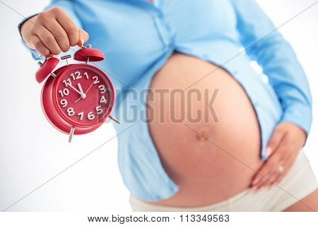 Counting hours expecting child birth. Motherhood concept. Pregnant woman holding alarm clock studio shot. poster