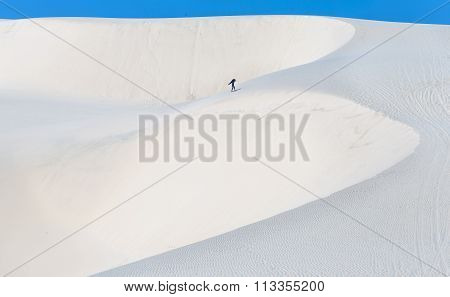 The solitary man crossing white sand dunes