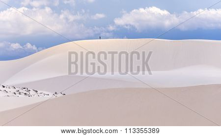 The little man was walking on beautiful white sand dunes