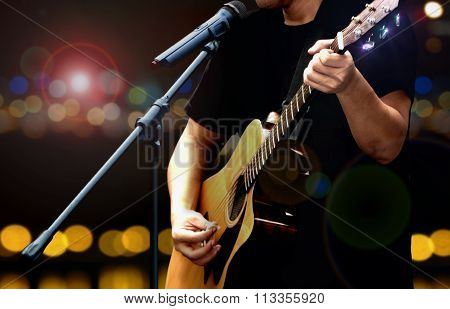 Guitarist On Stage Performing With Acoustic Guitar