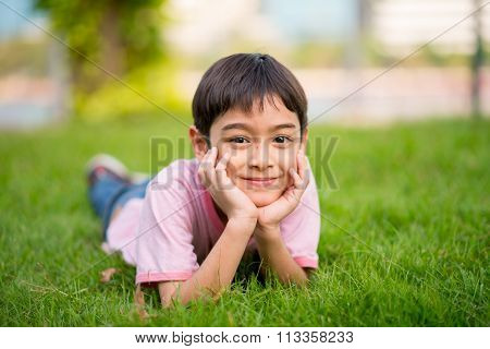 Little boy lay down on the grass with smile