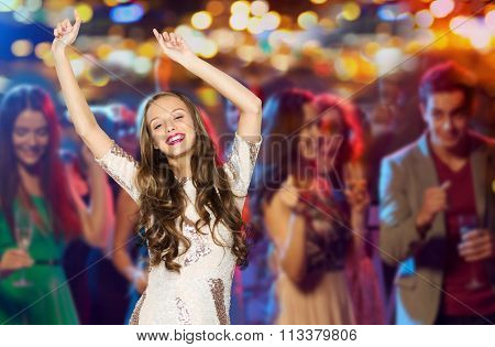 happy young woman or teen dancing at disco club