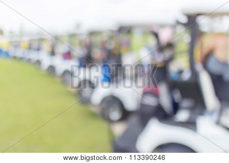 Blurred Photo Of Row Golf Cart And Caddy In Golf Course Waiting For Golfers.