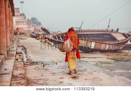 Poor Lonely Man Walking Past Famous Ganges River With Rustic Riverboats