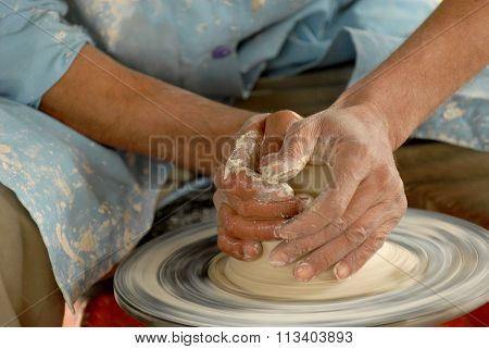 Pottery making close-up. Craftsman's hands shape clay into a fictility on a spinning wheel. poster