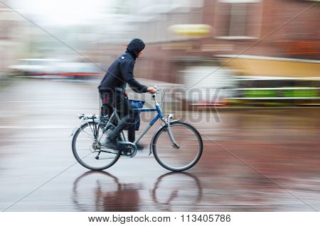 bicycle rider in the rainy city in motion blur