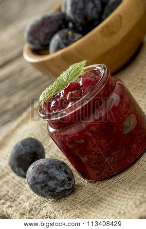 Setting With A Glass Jar Of Plum Marmalade On A Burlap Sac With Two Fresh Plums