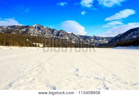 Mountain landscape with blue sky fluffy white clouds and frozen lake at Hyalite Reservoir Bozeman MT poster