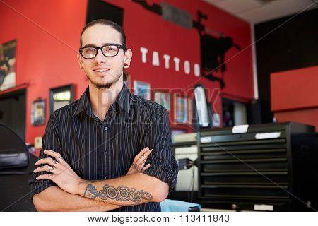 Portrait Of Tattoo Artist Standing Inside Parlor