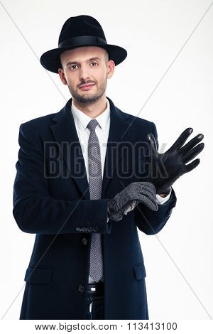 Attractive gentleman in black hat and coat putting on black leather gloves over white background