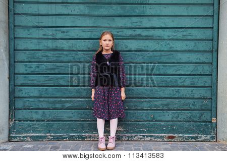 Outdoor fashion portrait of a cute little girl of 8 years old, wearing black dress and faux fur coat