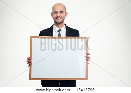 Cheerful handsome young businessman holding blank board over white background