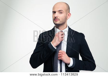 Handsome confident young business man in black suit  straightening his tie over white background