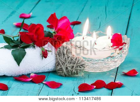 Spa composition with red roses, heat and candles