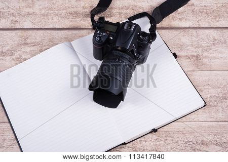 Photographers Workplace With Book And Camera On Wooden Table