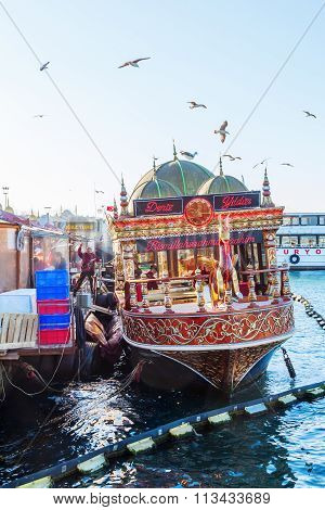 ISTANBUL, TURKEY - APRIL10,2015: fish restaurant boats at the banks of the Eminoenue district of Istanbul with unidentified people. Istanbul is the largest city in Turkey and famous travel destination