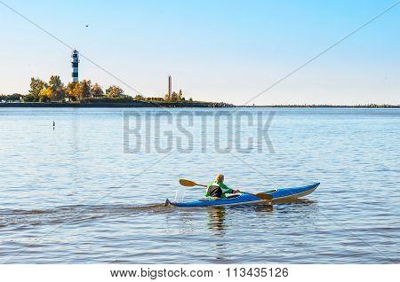 Man makes a trip by canoe on river Daugava near port of Riga