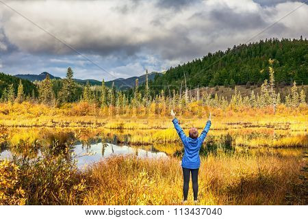 An elderly woman in awe of the beautiful nature on the shore of the lake. The lake reflects multi-colored autumn woods and mountains