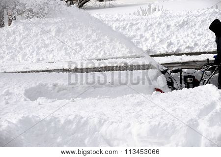 man operating snowblower to remove snow on driveway