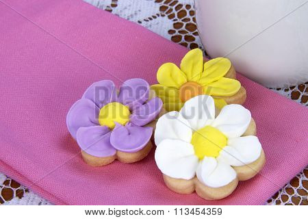 flower sugar cookies on pink napkin lace table cloth white cup