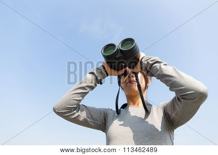 Young Woman looking though binoculars with clear blue sky
