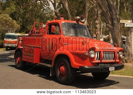 A vintage firetruck is on display at a local festival