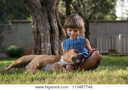 Little Boy Cuddling His Dog